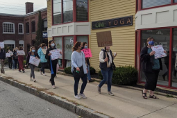 A group of teachers marches on the sidewalk in downtown Andover, Massachusetts.