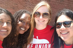 Selfie of four Baltimore teachers in front of a school.