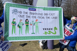 "Two nurses hold a green St. Patrick's Day banner that reads ""And the righteous did cast out the evil from the land."" The banner pictures a group of nurses chasing off a snake labeled Tenet."