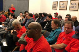 Meeting of DASH drivers, most of them seated and wearing red.