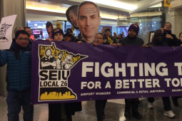 """Commercial office janitors, retail janitors, security officers, window cleaners, and airport workers march through the downtown Minneapolis skyway, carrying a banner that reads """"Fighting Today for a Better Tomorrow,"""" as part of SEIU Local 26's contract campaign."""