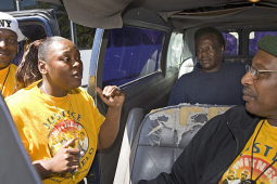Two workers speaking in a vehicle with others seated or around the vehicle.