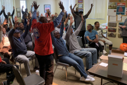 Strike authorization vote - people standing with arms raised.