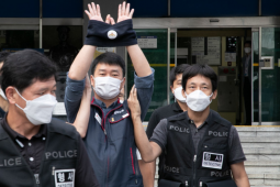 """Man in mask raises handcuffed hands in air, escorted by several other masked men whose jackets read """"POLICE"""""""