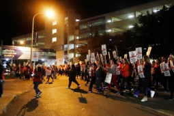 """Workers with """"On Strike"""" picket signs march past a hospital in the near-dark, silhouetted by one bright light."""