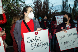 """Three women dressed in red hold hand-lettered signs: """"Safe Staffing Saves Lives"""" and """"Patients Over Profits"""""""