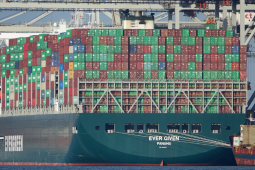 """Huge ship loaded with containers, viewed from stern which says """"Ever Given, Panama."""" In the background are port cranes."""