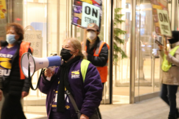"People in masks and purple SEIU 87 shirts picket in front of a bright window. Central person has a bullhorn. Others carry ""ON STRIKE"" signs and wear reflective vests."