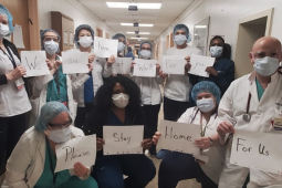 "Masked health care workers in a hospital hold signs reading: ""We... are... here... at... work... for.. you... Please... stay... home... for us."""