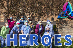 "Medial personnel gathered outside in back of a sign that says ""Heroes."""