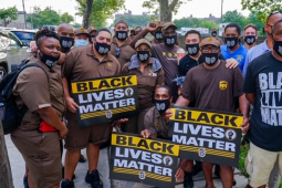 "crowd of workers, many in brown UPS uniforms, with ""Black Lives Matter"" signs"