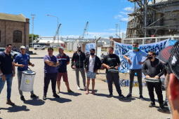 A group of workers, some holding drums, gathers in a circle outside a port.