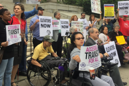 """Demonstrators, some in wheelchairs and some not, stand in front of a public building. Many are holding signs: """"ACCESSIBLE TRANSIT FOR ALL,"""" """"ELEVATORS NOW,"""" """"STRANDED BY CUOMO"""""""
