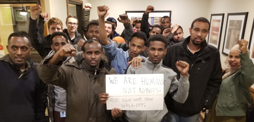 Amazon workers with fists raised gathered around a sign.