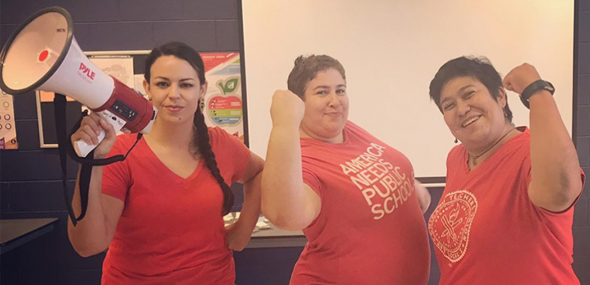 Three Chicago teachers, one with bullhorn and two with arms flexed.