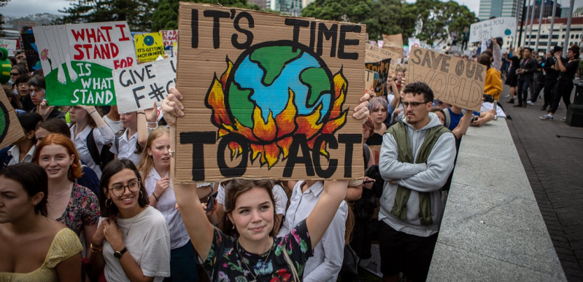 "New Zealand students hold signs with slogans like ""It's Time to Act,"" with a drawing of the earth being consumed by flames, during a school strike in March 2019."