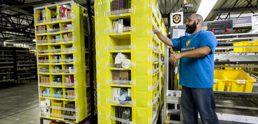 A worker in an Amazon warehouse picks items from a yellow shelf mounted on a robot.