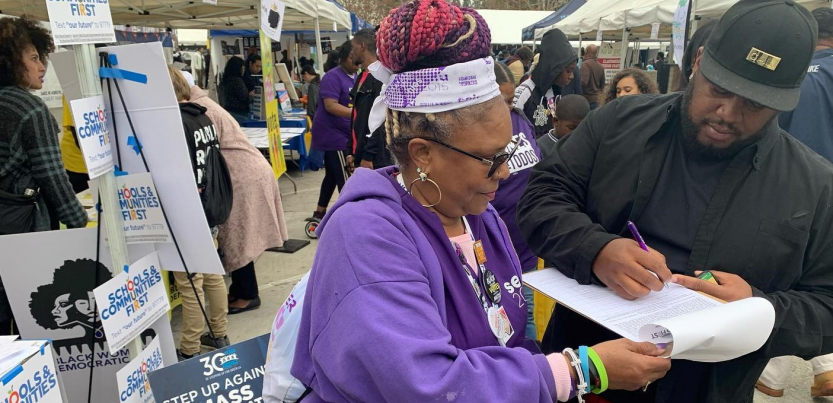 "Outdoors at a public event, a woman in SEIU purple holds a clipboard while a man signs. The booth behind her is decked witht ""SCHOOLS AND COMMUNITIES FIRST"" signs and one that says ""Step up against mass incarceration."""