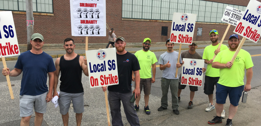 """Strikers stand with signs """"Solidarity,"""" """"Local S6 on strike"""" """"Local S6 IUMSWA/IAM [obscured] on strike against Bath Iron Works"""""""