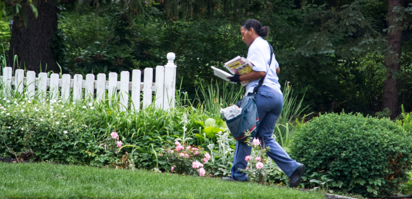 A Black woman letter carrier walks across a lawn, in front of a white picket fence, carrying the mail
