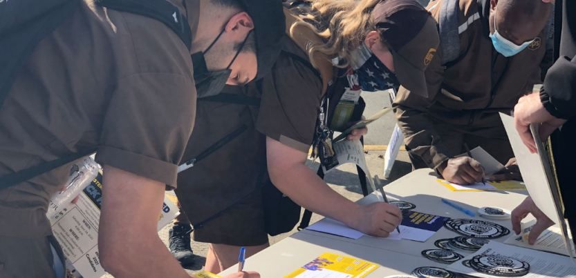 Three people in UPS uniforms and masks bend over a table of campaign literature, signing cards