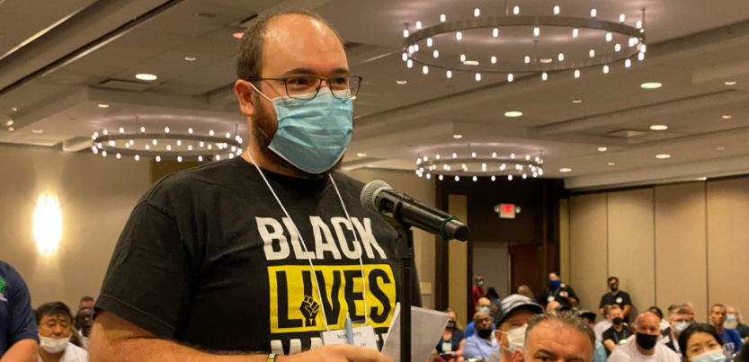 """white man in mask at mic in hotel banquet room, wearing """"Black Lives Matter"""" shirt, speaks as other people look on"""