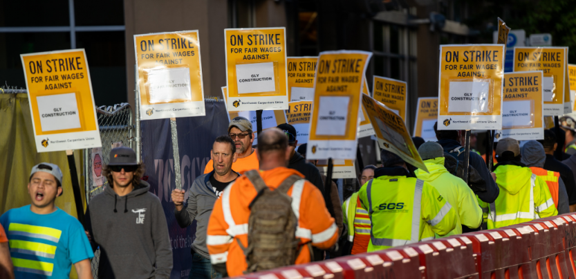 """Picketers in high-visibility garb file alongside a plastic barrier. Printed signs read """"ON STRIKE FOR FAIR WAGES AGAINST GLY CONSTRUCTION"""""""