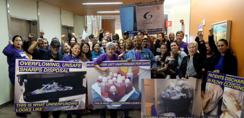 """Big crowd of members in a hallway, many fists in air. Front row holds oversized photo signs with captions: """"OVERFLOWING, UNSAFE SHARPS DISPOSAL: THIS IS WHAT UNDERFUNDING LOOKS LIKE."""" """"BLO{***}ATER LEFT UNATTENDED FOR DAYS: THIS IS WHAT UNDERSTAFFING LOOKS LIKE."""" """"PATIENTS DISCHARGED IN FILTHY CLOTHING.""""]"""