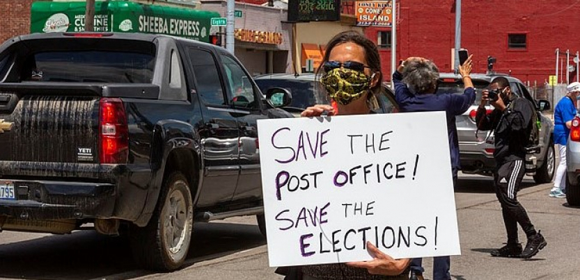 "A masked protester holds a sign: ""Save the Post Office! Save the Elections!"" Behind the person, traffic and a ""Coney Island"" (diner) across the street"