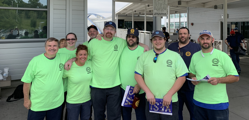 Group of workers in matching green T-shirts outside the plant