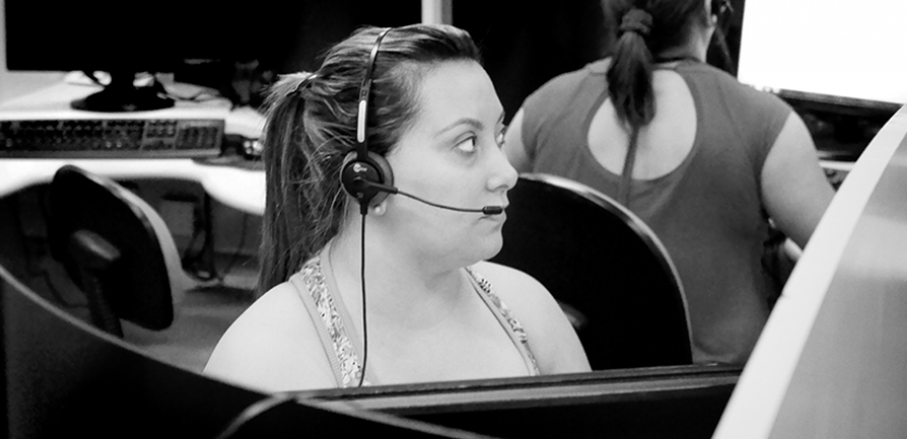 female call center worker with headset at cubicle, other workers in background