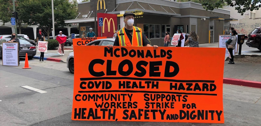 "masked worker in front of mcdonald's holds big orange sign: ""MCDONALD'S CLOSED, COVID HEALTH HAZARD, COMMUNITY SUPPORTS WORKERS STRIKE FOR HEALTH, SAFETY AND DIGNITY"""