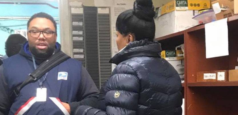 Two postal workers talking to each other inside an office.