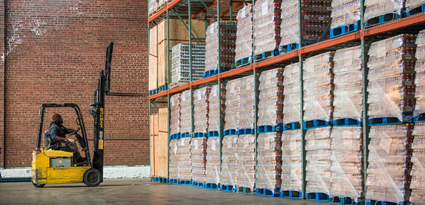 Worker with forklift in front of cases of pallets on shelves in warehouse