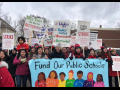 "Strikers carry a banner ""Fund Our Public Schools"" with a rainbow of faces. Picket signs say ""Strike"" and ""It's Time to Use Our Outside Voice."" One kid is carried on an adult's shoulders."