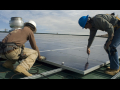 Two workers installing solar energy at Garfield County Fairgrounds