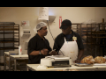 Two bakery workers talk in a kitchen.