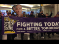 "Commercial office janitors, retail janitors, security officers, window cleaners, and airport workers march through the downtown Minneapolis skyway, carrying a banner that reads ""Fighting Today for a Better Tomorrow,"" as part of SEIU Local 26's contract campaign."