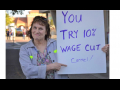 """woman outdoors holds sign: """"You try 10% wage cut Carmel!"""""""