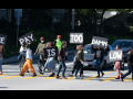 """grad students blocking traffic in the street with signs that read """"The Pay Is Too Damn Low"""""""