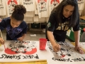 "Two people painting signs that say ""public schools are the heart of the community"""