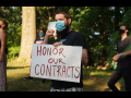 "Masked person holding sign ""Honor Our Contracts"" in front of trees, other masked demonstrators"
