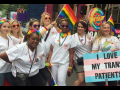 "Nurses in white scrubs with rainbow flags and accessories; one carries a sign ""I Love My Trans Patients"" with the trans flag (pastel blue, pink, and white stripes)"