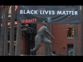 A Black Lives Matter banner hangs behind a statue of Willie Mays at Oracle Park.