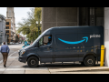 Amazon van exiting a building, about to turn onto a city street, with pedestrian crossing in front