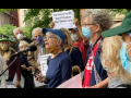 """A group of older people in masks stands outside. The person in the middle is speaking into a mic. Someone behind her holds up a printed sign: """"City Retirees Say NO, Don't Privatize Our Senior Care!"""""""