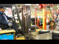 A worker drives a forklift inside a John Deere plant