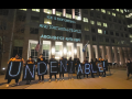 "People holding lit signs spelling out ""UNDENIABLE"" stand in front of a building. On the building are projected the words: ""ICE IS DEPORTING AND TORTURING PEOPLE! ABOLISH ICE AND CBP!"""