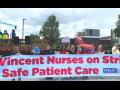 """People outside hold a huge banner: """"St. Vincent Nurses on Strike for Safe Patient Care; MNA"""""""