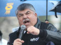Richard Trumka speaking animatedly into a microphone, under an umbrella, at a 2016 demonstration.